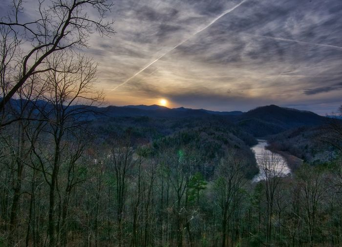 Sunset over Little Tennessee River Bare Tree Beauty In Nature Built Structure Cloud - Sky Contrails Dusk Environment Landscape Mountain Mysterious Nature No People Outdoors Plant River Scenics - Nature Sky Sun Sunset Tranquil Scene Tranquility Tree Valley Vapor Trail