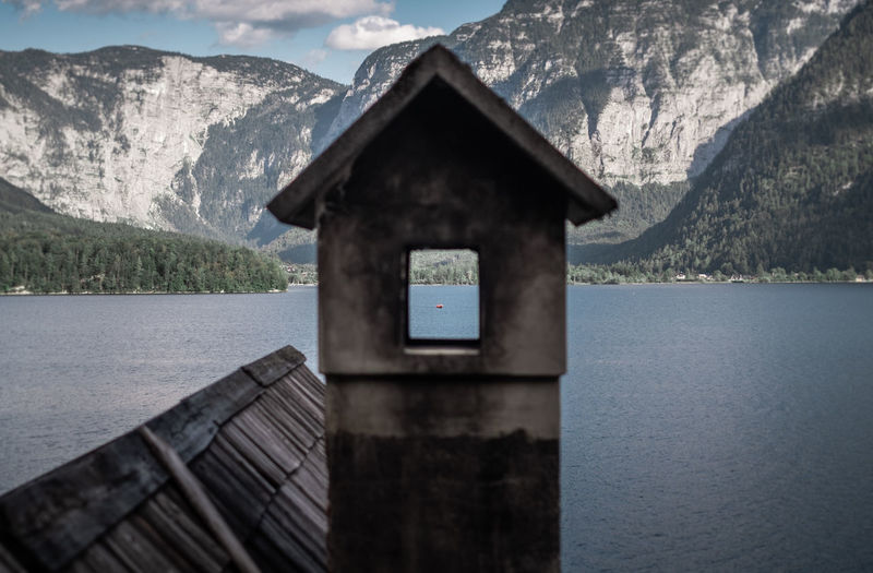 Built structure by lake against mountains