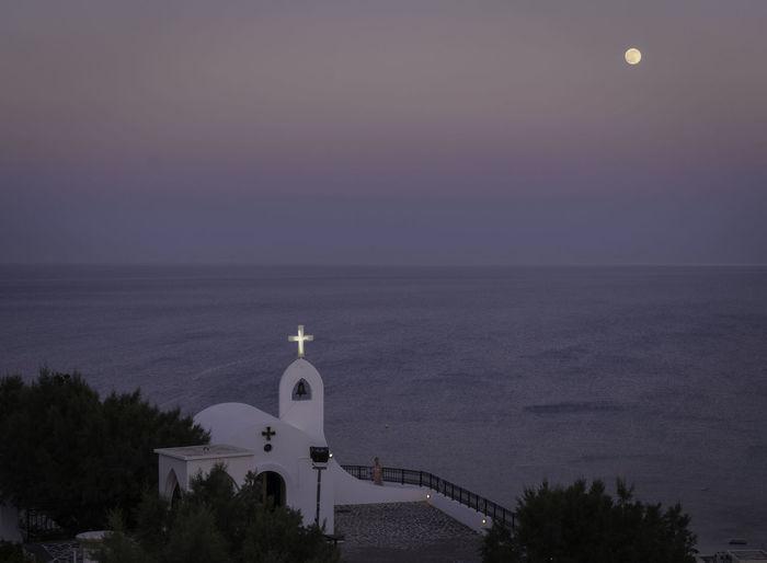 Illuminated cross on chapel by sea against sky at dusk