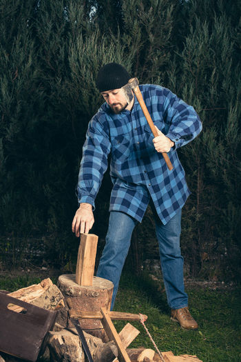 Full length of lumberjack chopping wood from axe against trees at forest