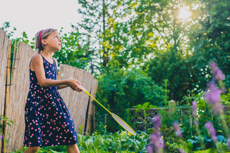 Side view of girl playing badminton against trees in yard