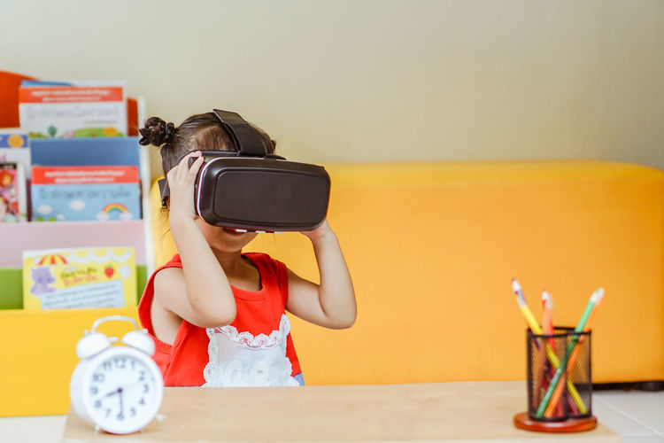 Close-up of cute girl wearing virtual reality simulator