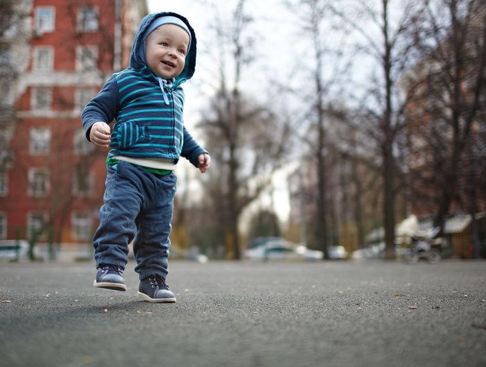 Smiling Baby Boy Walking On Street