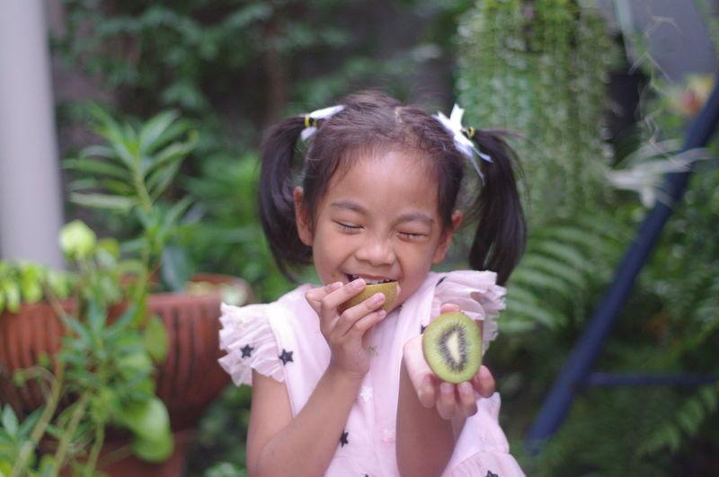 Close-up of smiling girl holding kiwi against plants