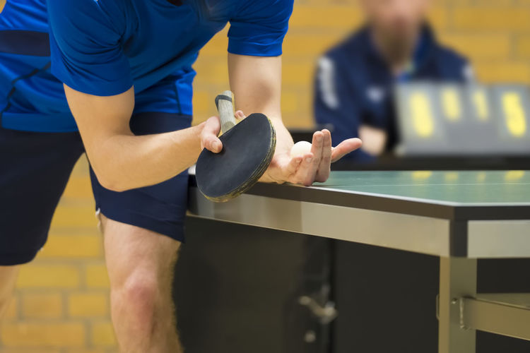 Table Tennis player serving Sport Focus On Foreground Midsection Real People Men Standing Lifestyles One Person Clothing Holding Front View Strength Indoors  Healthy Lifestyle Determination Exercising Sports Clothing Competition Leisure Activity Table Tennis Serving Ping Pong