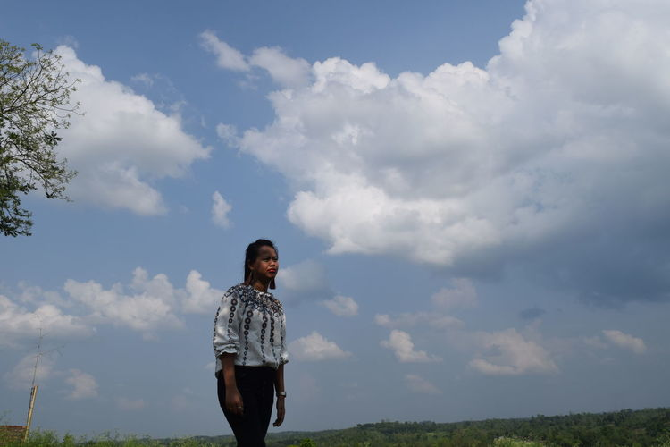 Young Woman Standing On Field Against Cloudy Sky