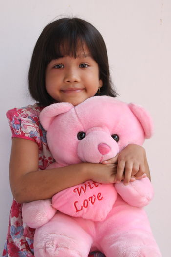 Portrait Of Cute Girl With Pink Teddy Bear Sitting Against Wall