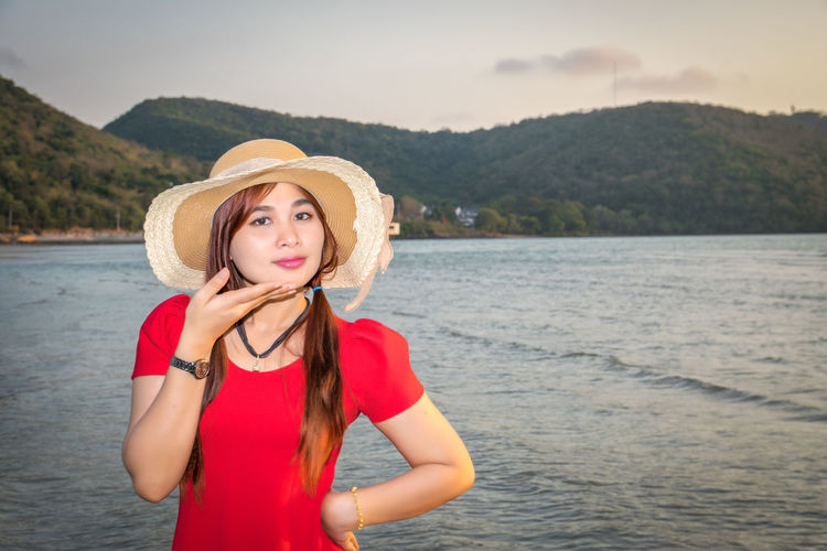 Portrait of beautiful woman with hand on chin standing on beach