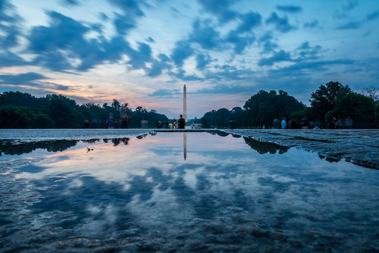 Reflection of washington monument in puddle against sky