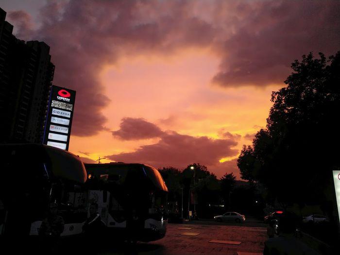 Car on street against dramatic sky