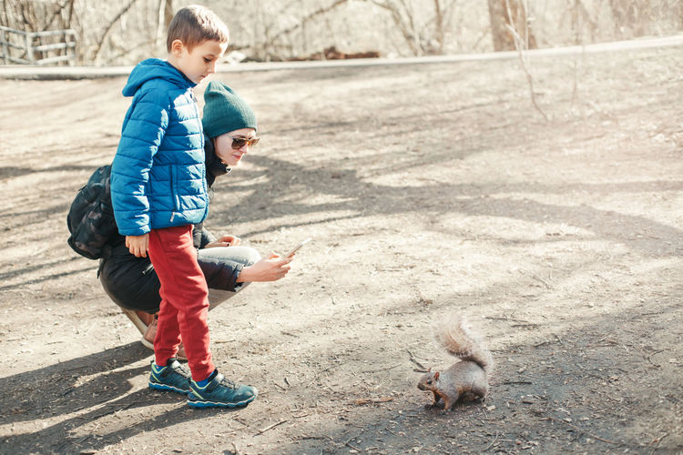 Mother and son taking picture photo of squirrel in park. mom and kid snapping photos of wild animal