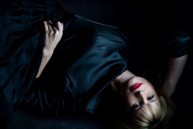 Close-up of young woman lying down against black background