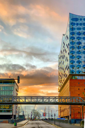 Low angle view of bridge and buildings against sky during sunset