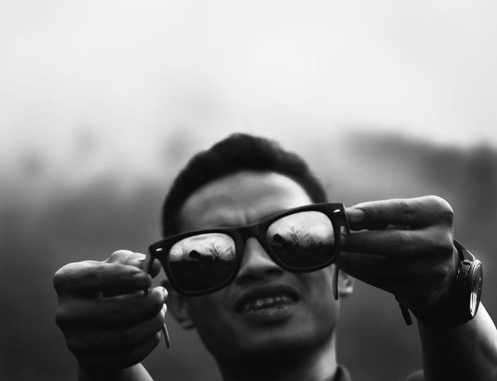 Close-up of man holding reflective sunglasses
