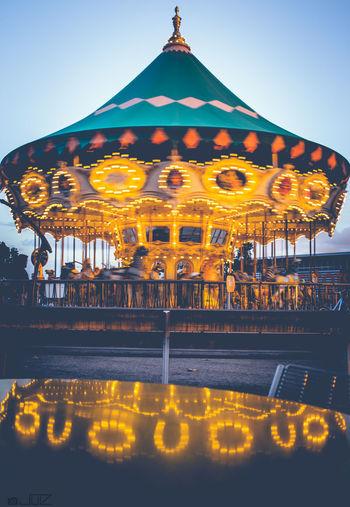 Illuminated carousel against clear sky at night