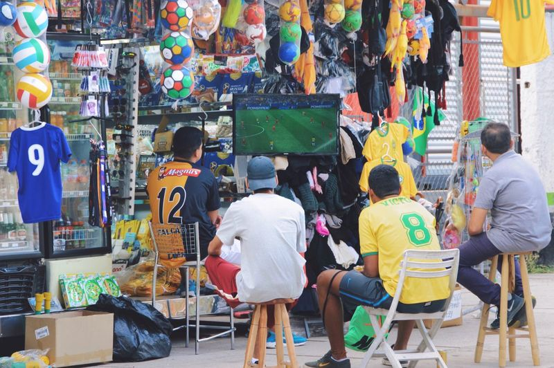 World Cup 2018 City Life World Cup Togetherness Colorful City Life Watching Tv Soccer Street Photography Streetphotography Men Real People Group Of People Rear View Adult People Women Business Sitting Retail  Small Business Full Length Market Day Casual Clothing Multi Colored Lifestyles Seat For Sale The Street Photographer - 2018 EyeEm Awards Love The Game