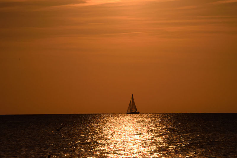 Beauty In Nature Boat Gold Colored Horizon Over Water Nature Nautical Vessel Orange Color Outdoors Reflection Sailboat Sailing Scenics Sea Silhouette Sky Sun Sunlight Sunset Tranquil Scene Tranquility Transportation Travel Destinations Vacations Water Yacht