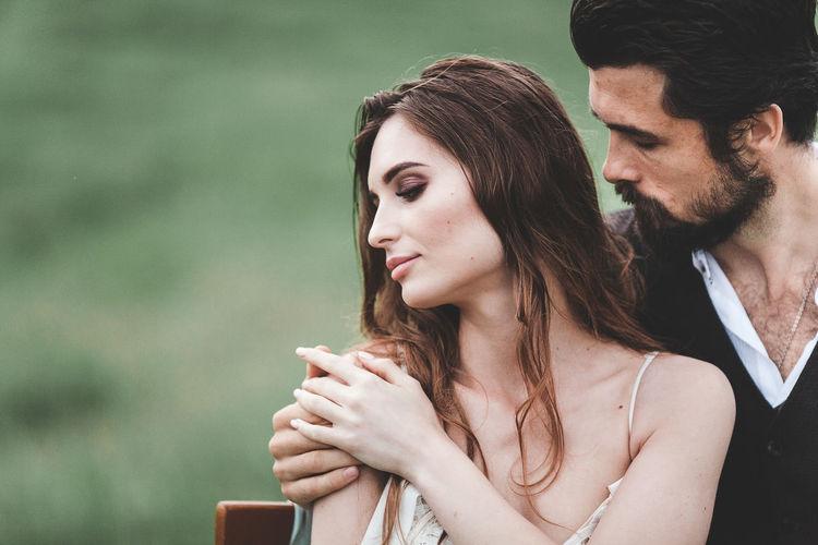 Close-Up Of Wedding Couple Romancing On Field