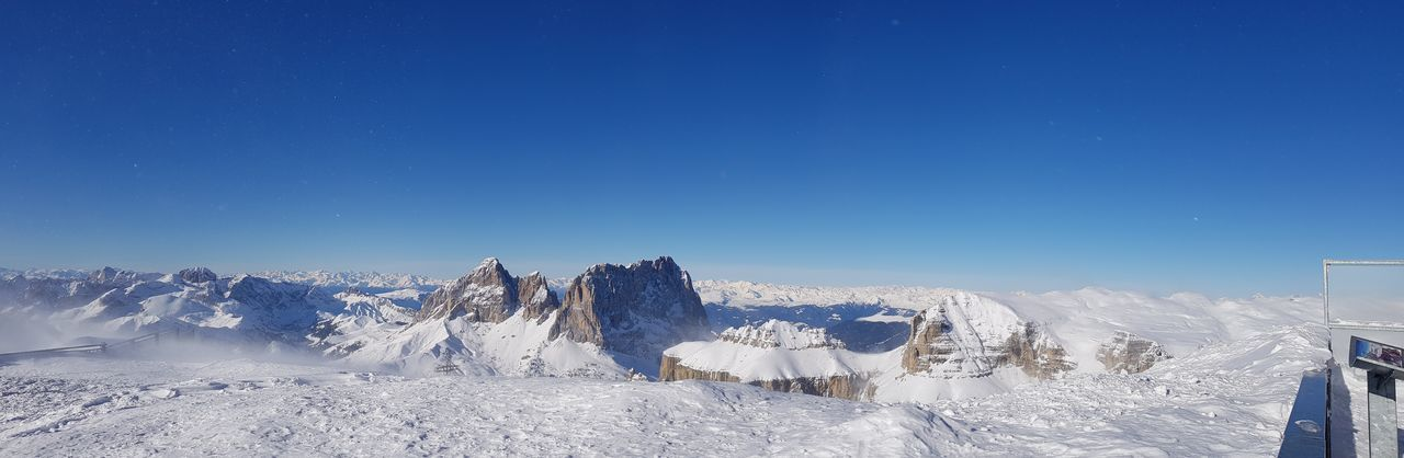 Panoramic view of snow covered landscape against clear blue sky
