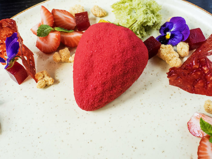 Strawberry shaped almond sponge cake with fruits in plate on table