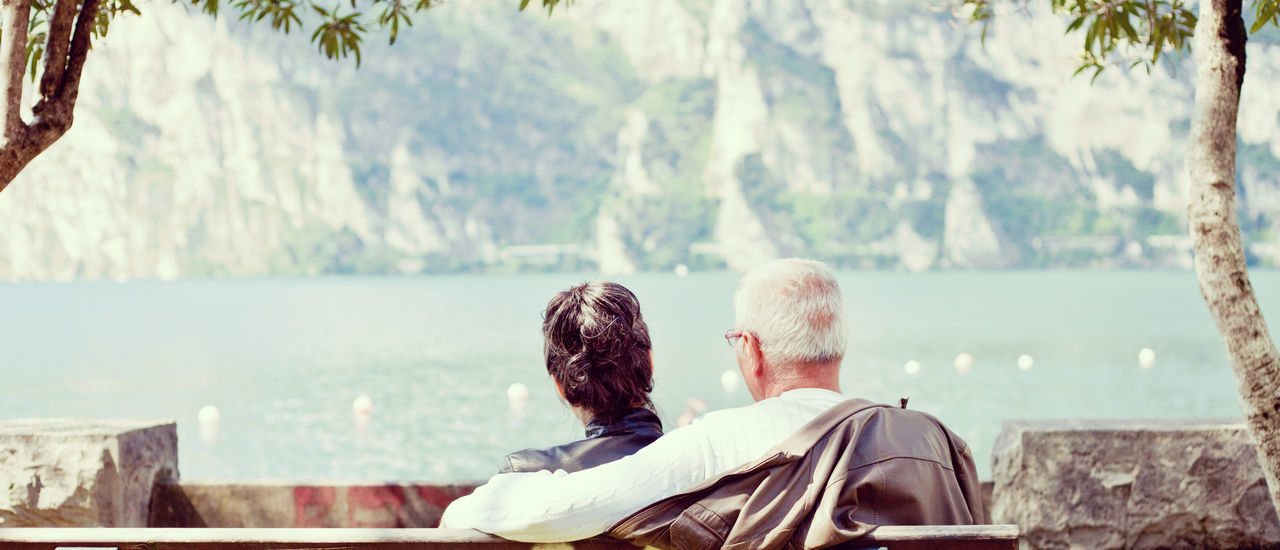 Rear View Of Couple Relaxing On Bench