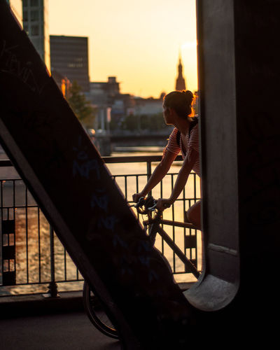 Woman riding bicycle on bridge in city during sunset
