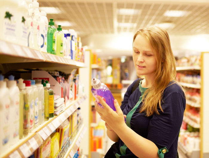 Woman buying soap dispenser in supermarket