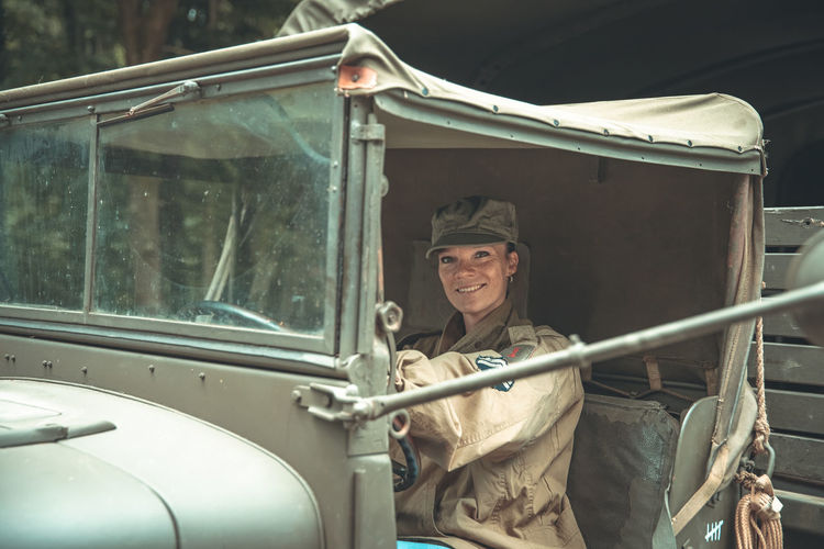 Portrait of army soldier sitting at vintage car