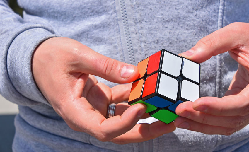 Midsection Of Man Holding Puzzle Cube