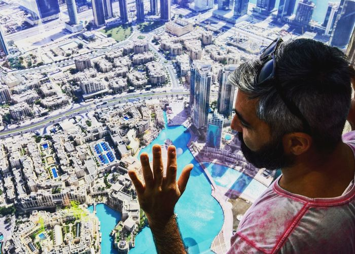 High Angle View Of Man Waving Hand Above Cityscape