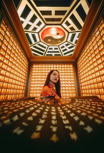 Full length portrait of woman standing against ceiling