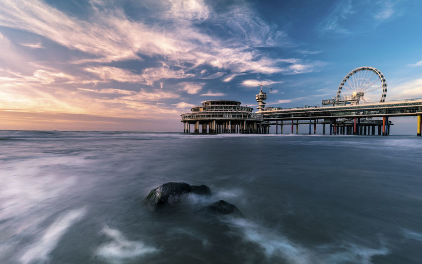 Pier by sea against cloudy sky during sunset