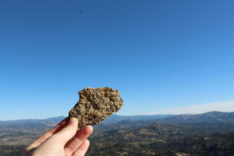Cropped hand holding rock against clear blue sky