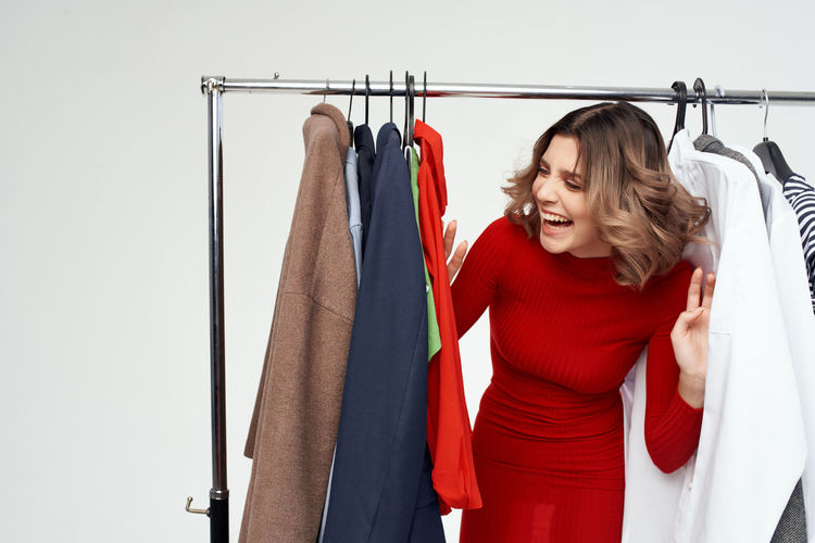 Happy young woman hanging on rack in store
