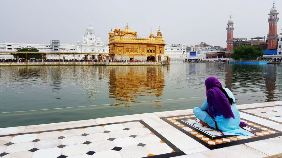 Woman sitting at lakeshore against golden temple