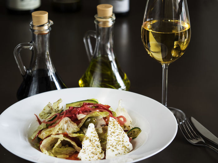 Close-up of greek salad in plate by wine served on table