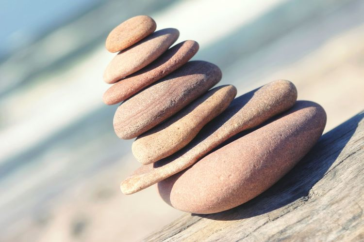 Close Up Of Stacked Stones On Wood