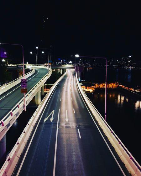 Illuminated Bridge Over Road In City At Night