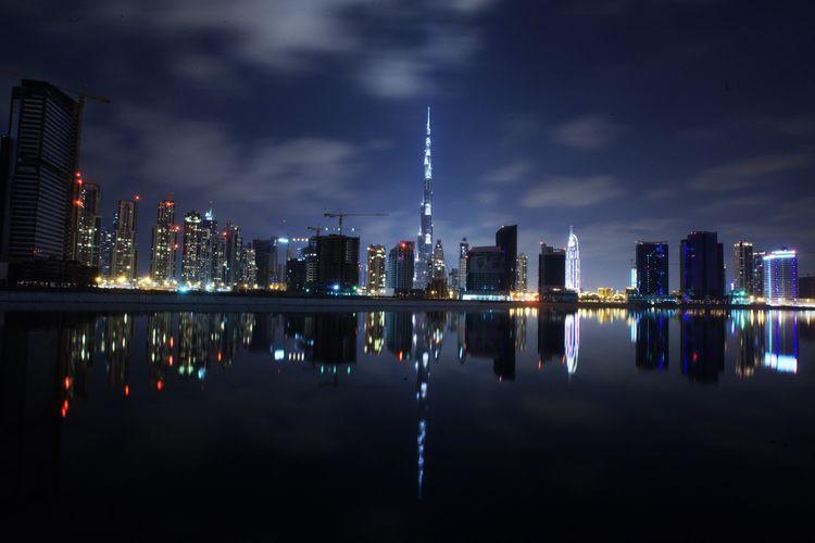 Burj Khalifa By Lake In Illuminated City At Night