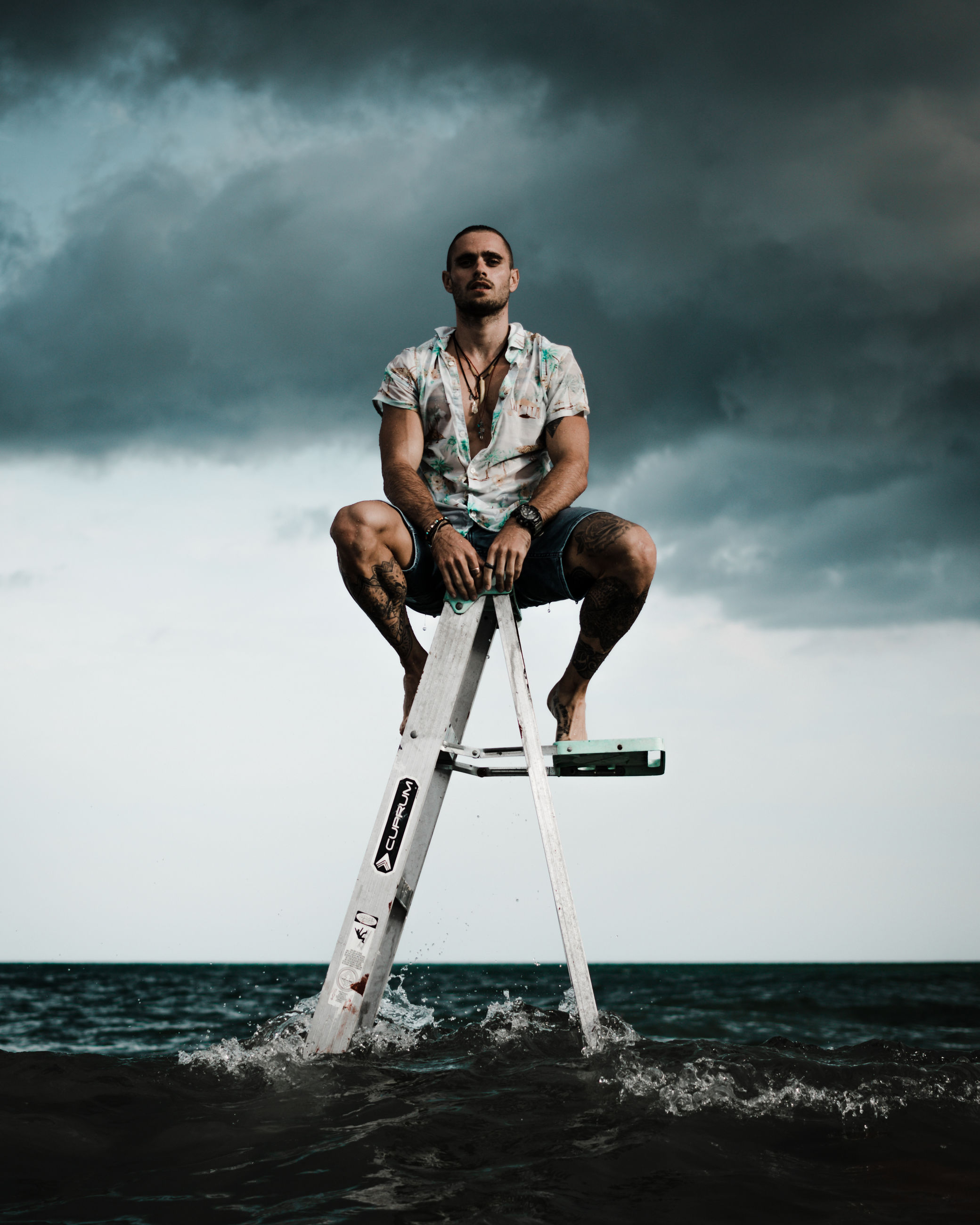 adult, cloud, one person, sky, water, full length, sea, men, nature, sitting, sports, young adult, overcast, copy space, storm, ocean, person, land, ladder, strength, outdoors, storm cloud, horizon over water, horizon, blue, holding, motion, surfing