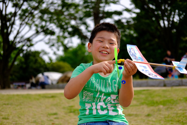 Portrait of happy boy holding toy airplane in park