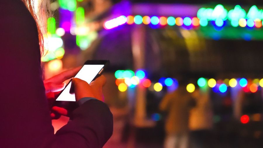 Midsection Of Woman Using Smart Phone In City At Night