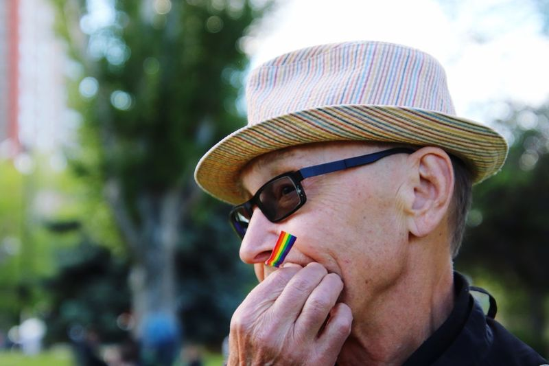 Close-Up Of Woman In Hat And Sunglasses With Small Rainbow Flag