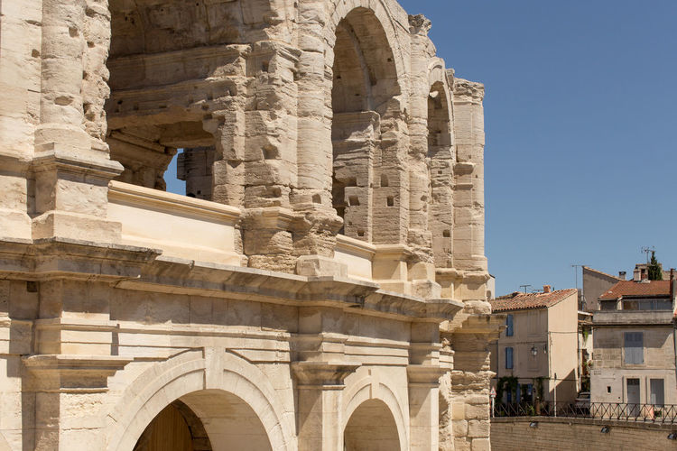 High section of the Arles Amphitheatre, a Roman arena. Arch Architectural Column Architectural Feature Architecture Blue Building Exterior Built Structure City Clear Sky Day Exterior Façade Famous Place Historic History Low Angle View National Landmark Outdoors Stone Material Tall - High Tourism Travel Destinations