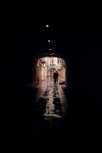 Silhouette people in illuminated tunnel