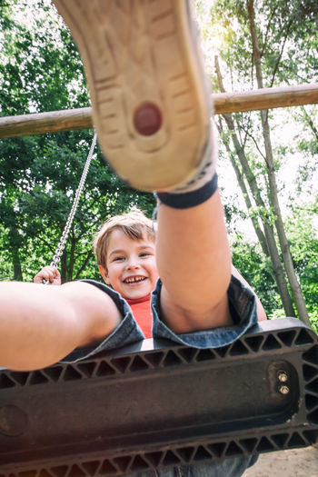 Portrait Of Smiling Boy On Swing At Playground