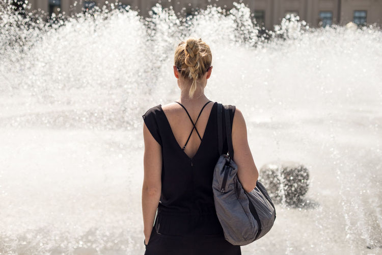 Rear view of woman standing in water
