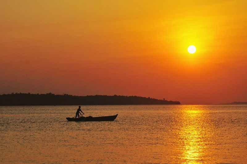 Silhouette Fisherman Boating On Sea During Sunset