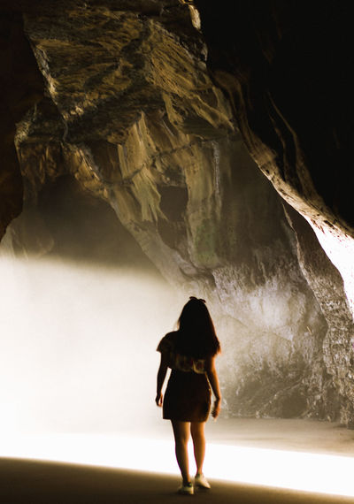 Rear view of woman standing in cave
