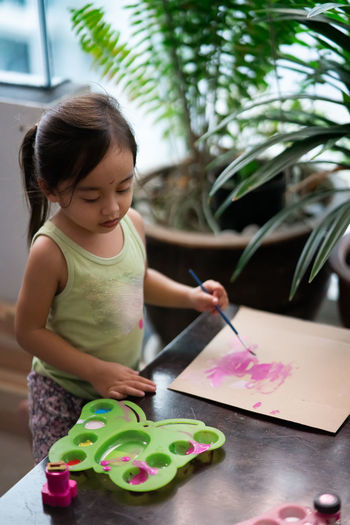 High angle view of girl painting on paper